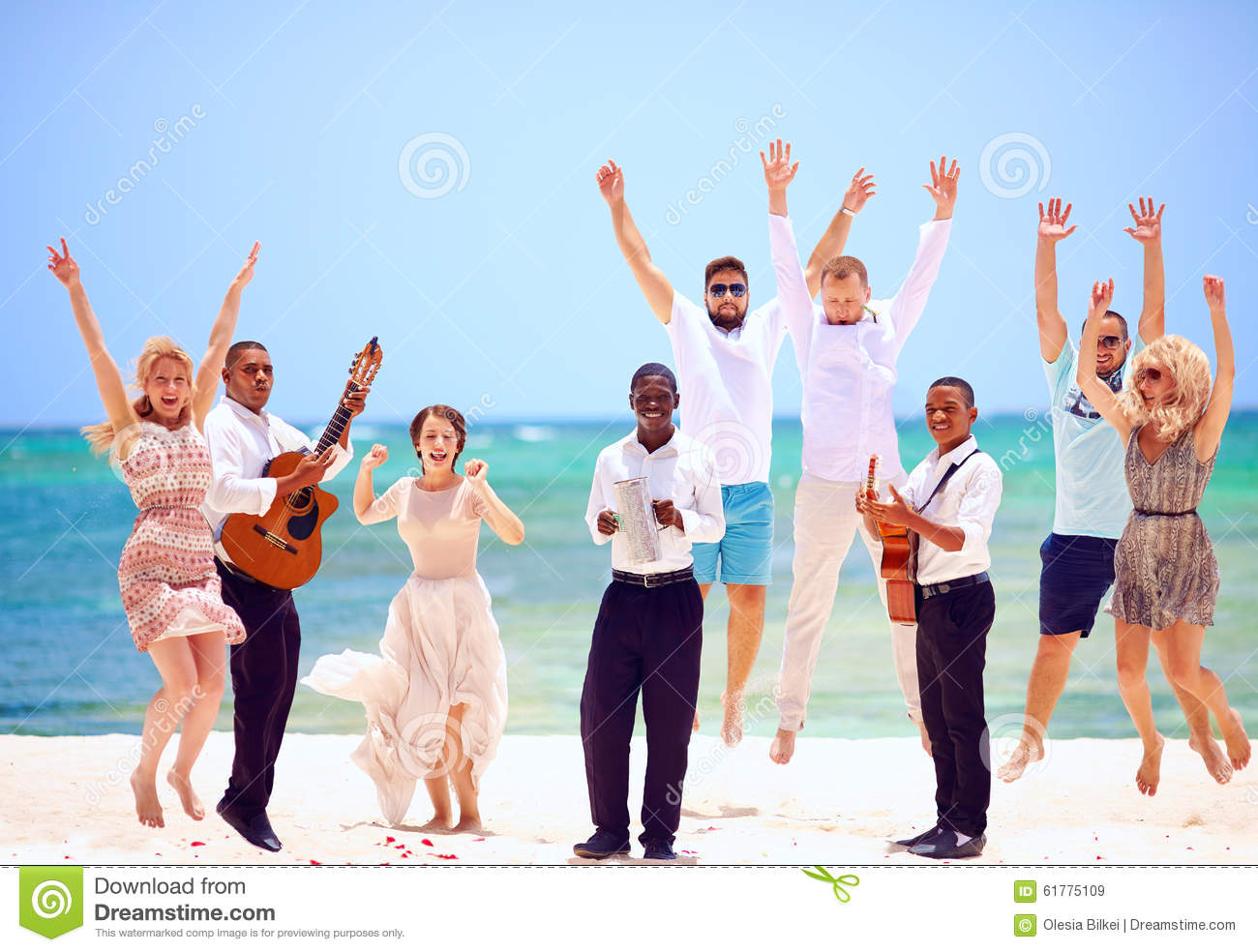 Group of happy people on celebration the exotic wedding with musicians, on tropical beach