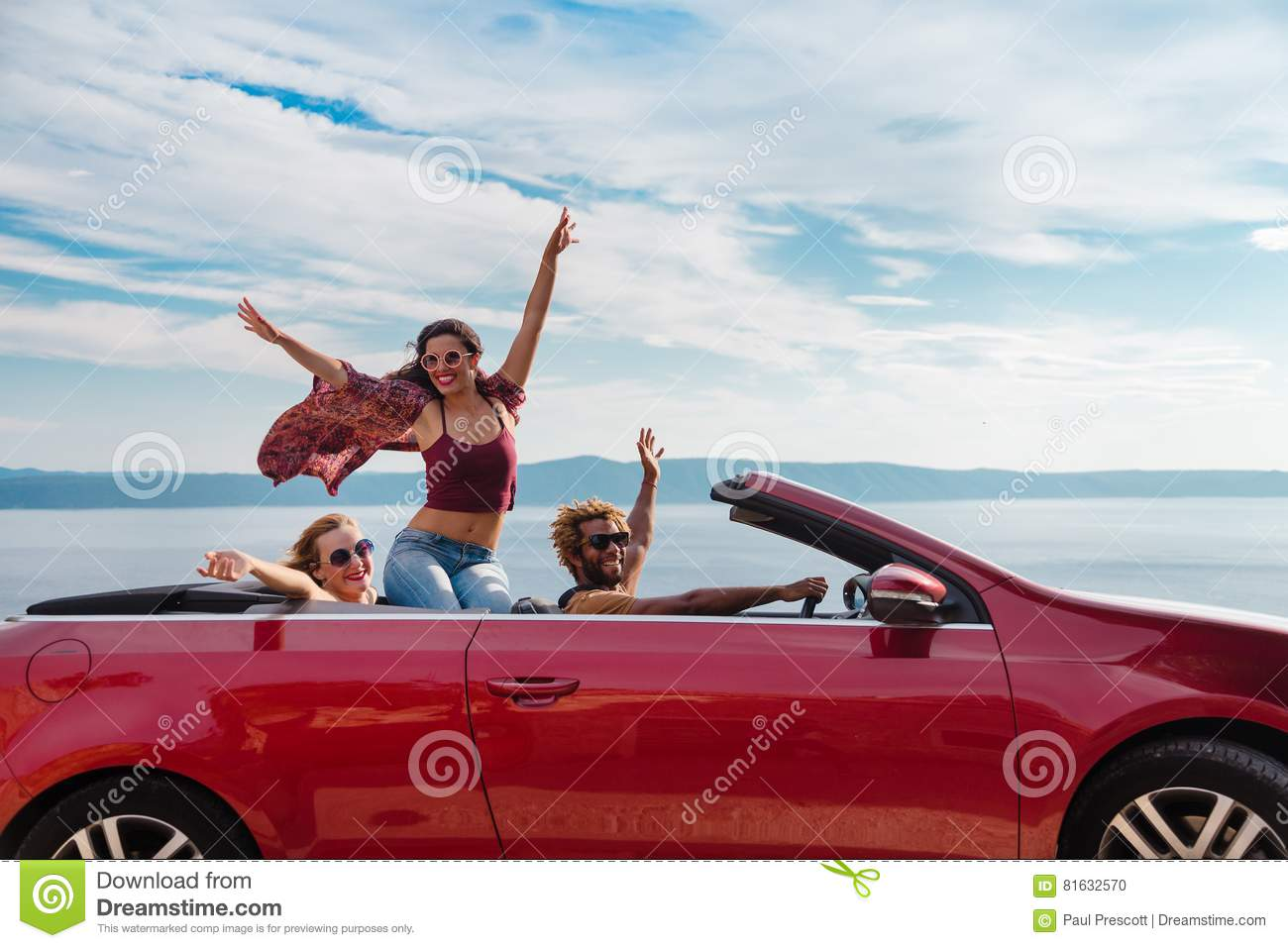 Group of happy people in red convertible car.