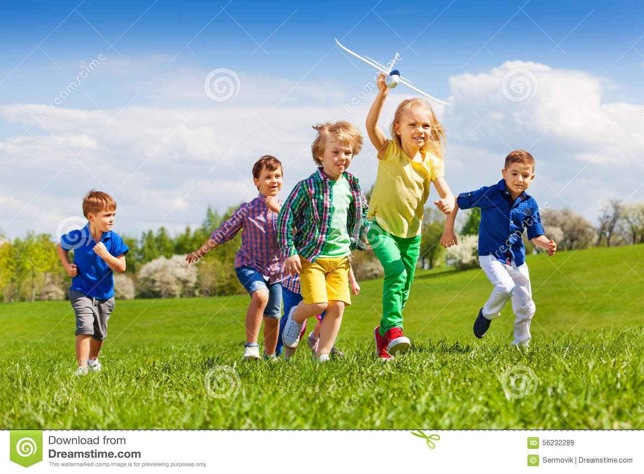 Group of happy running kids with white airplane