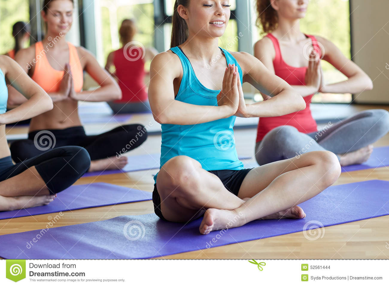 Group Of Happy Women Meditating On Mat In Gym Stock Photo