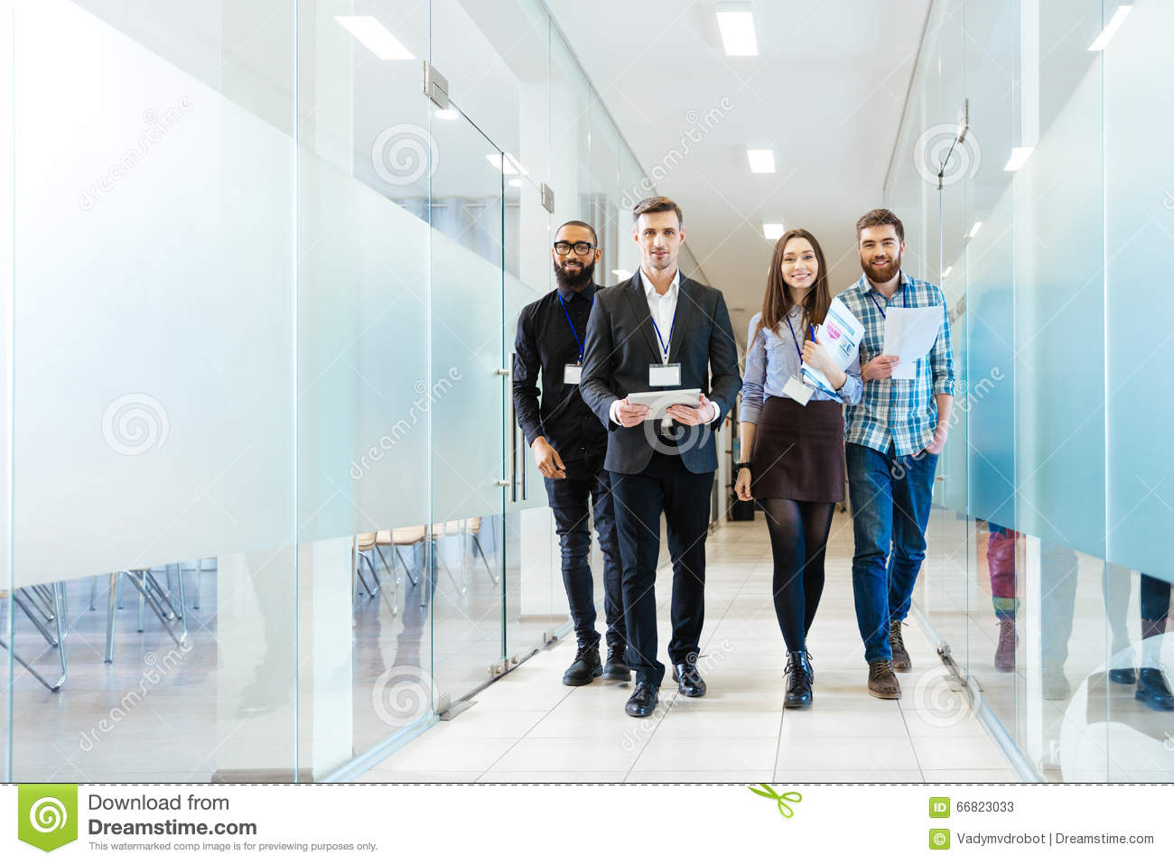 Group of happy young business people walking in office together