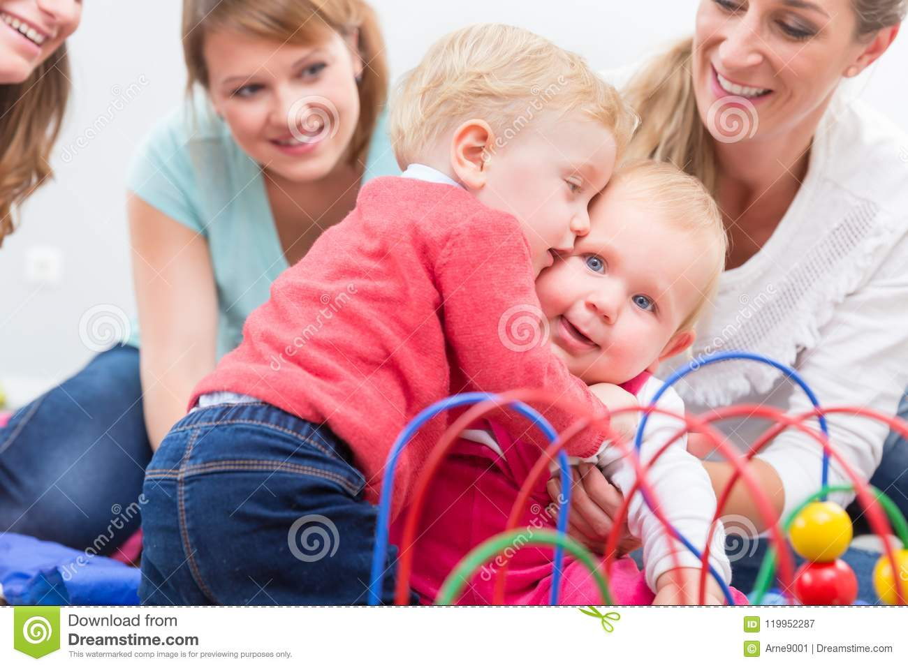 Group of happy young mothers watching their cute and healthy babies play