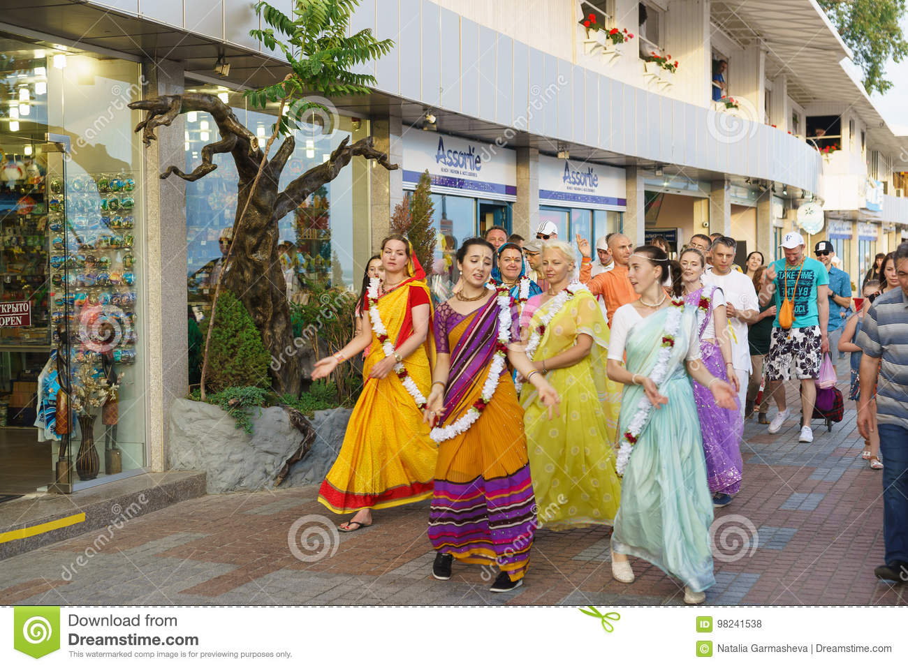 A Group of hare Krishnas singing and dancing are on the embankment of the resort town