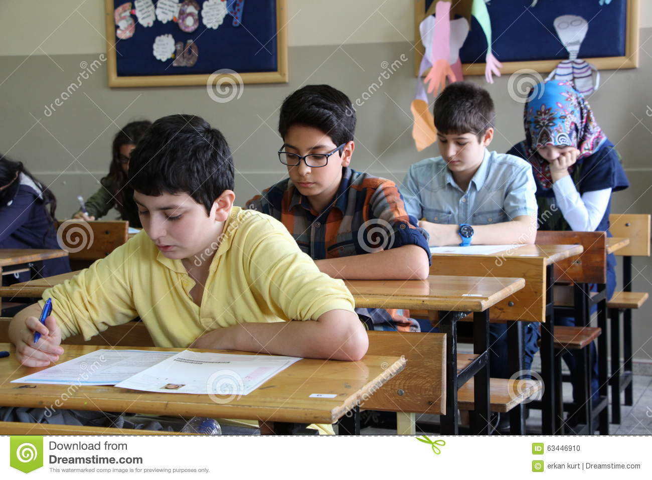 group of high school students taking a test in classroom
