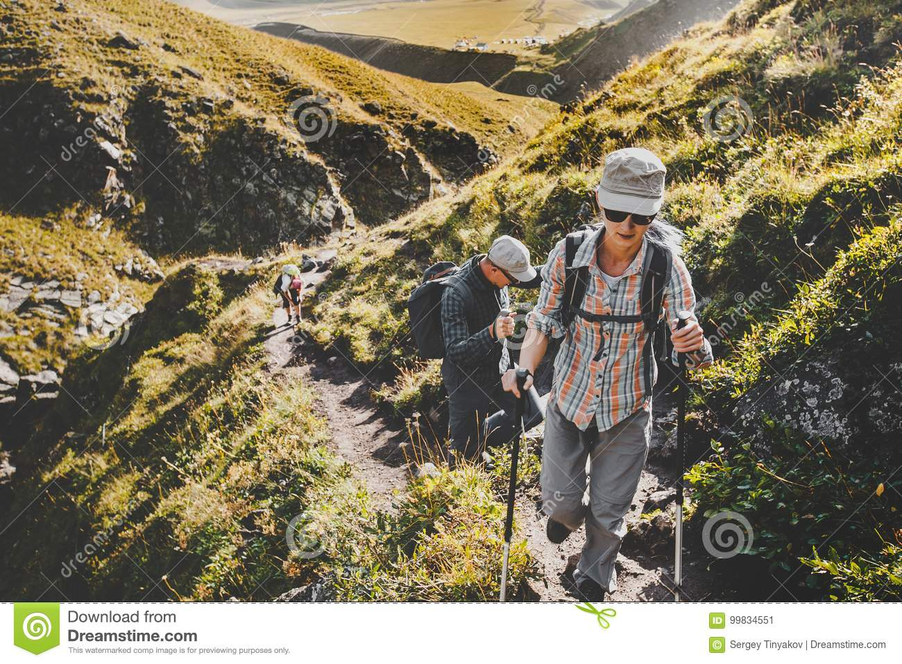 Group Of Hikers Walking Along In Summer Mountains, Journey Travel Trek Concept
