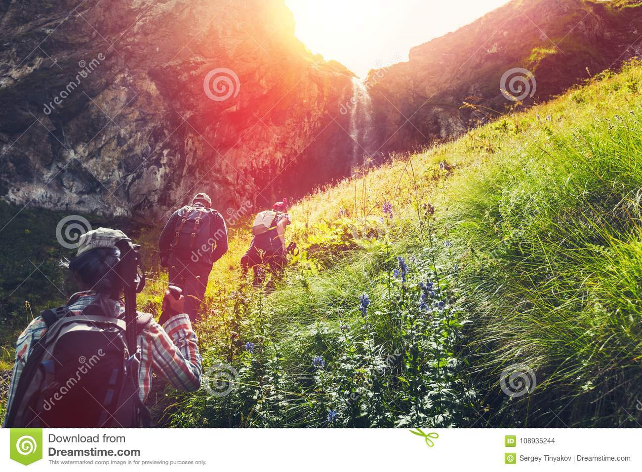 Group Of Hikers Tourists Walking Uphill To Waterfall. Travel Adventure Outdoor Concept
