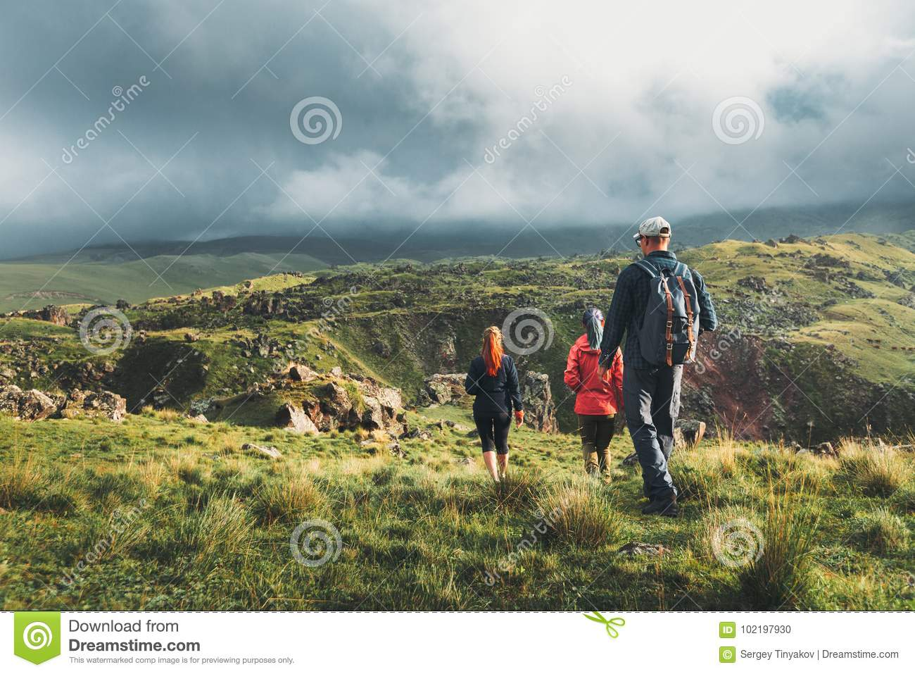 Group Of Hikers Walking Along The Green Hills, Rear View. Travel Tourism Discovery Concept