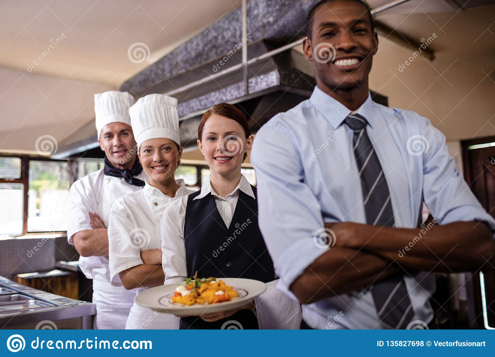 Group of hotel staffs standing with armas crossed in kitchen