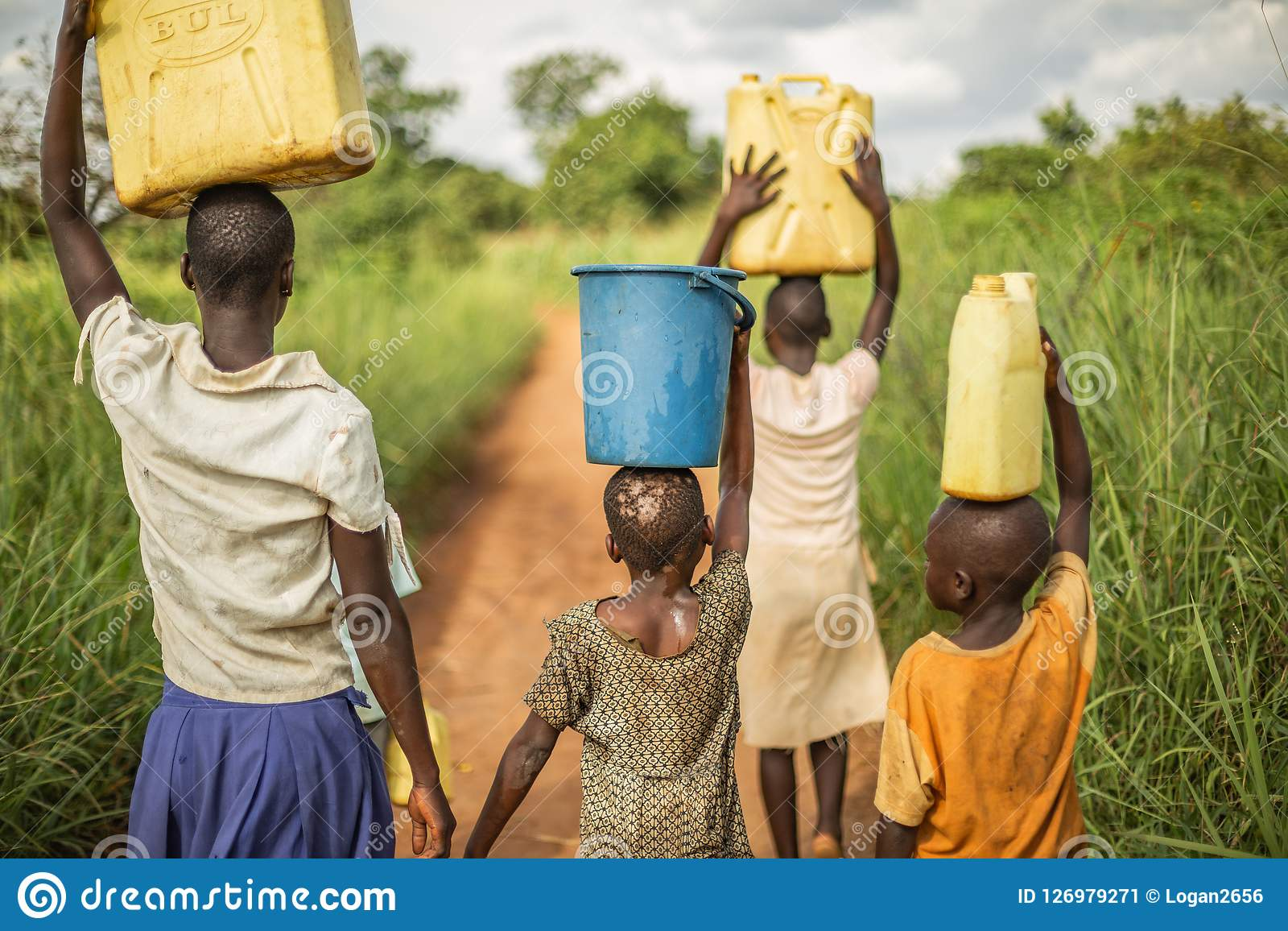 Group if young African kids walking with buckets and jerrycans on their head as they prepare to bring clean water back to their vi