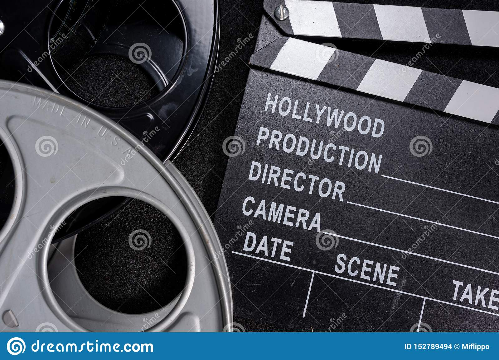Movie clapper and film reel on a wooden background
