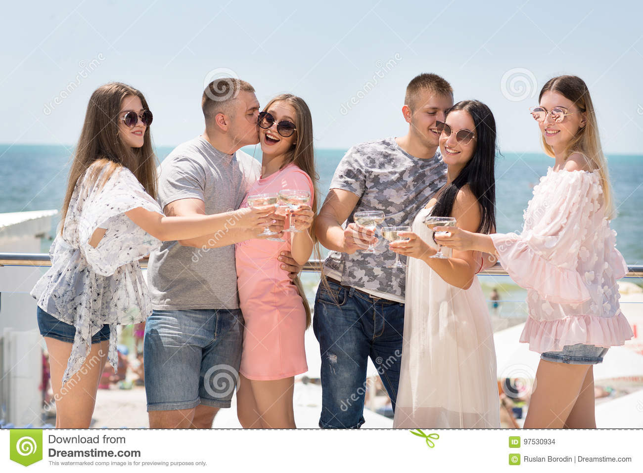 A group of joyful friends relaxing on a vacation. Pretty girls and strong men on a blue sky background. Friendship