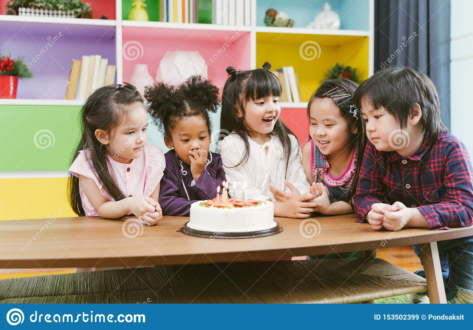 Group of kids enjoying a birthday party blowing out the candle on cake.