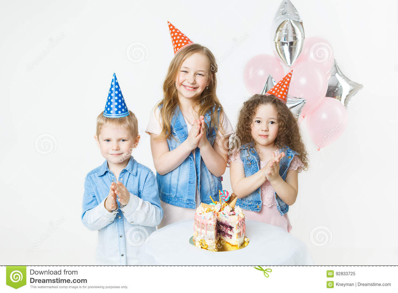 Group of kids in festive caps clap their hands near birthday cake, balloons on background
