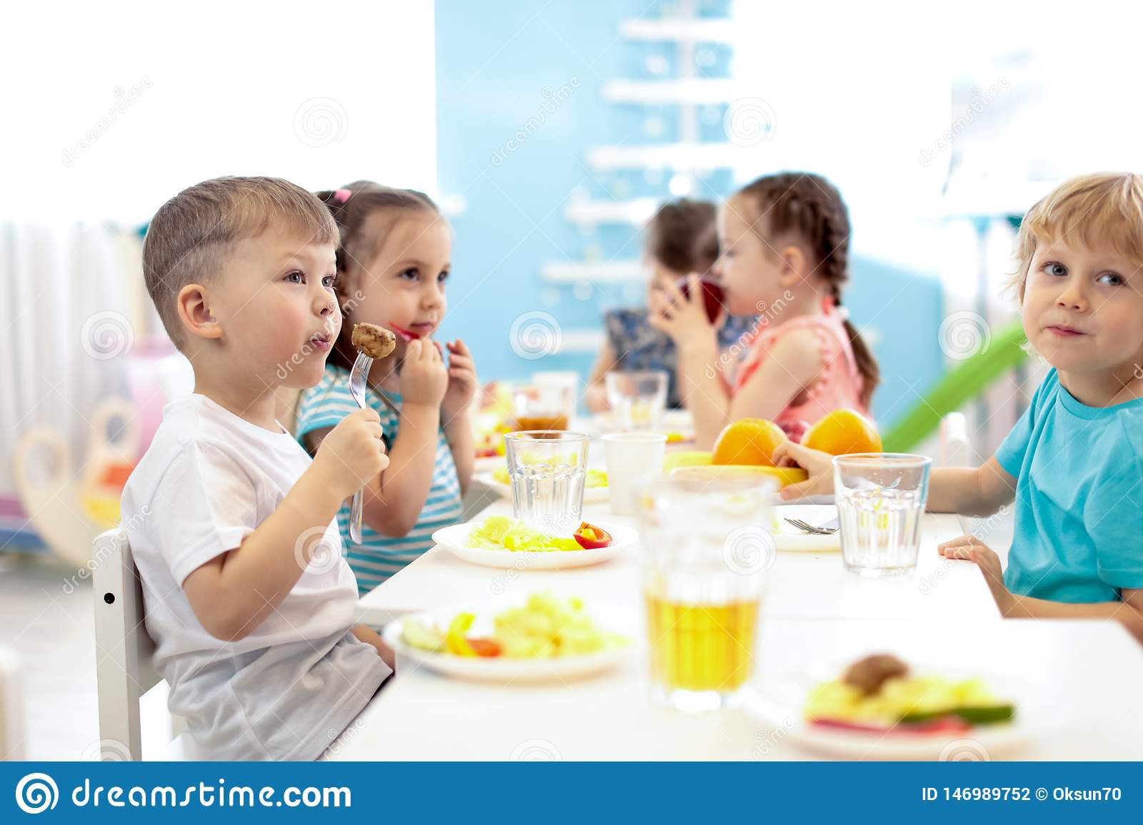 Kids have a lunch in daycare centre. Children eating healthy food in kindergarten