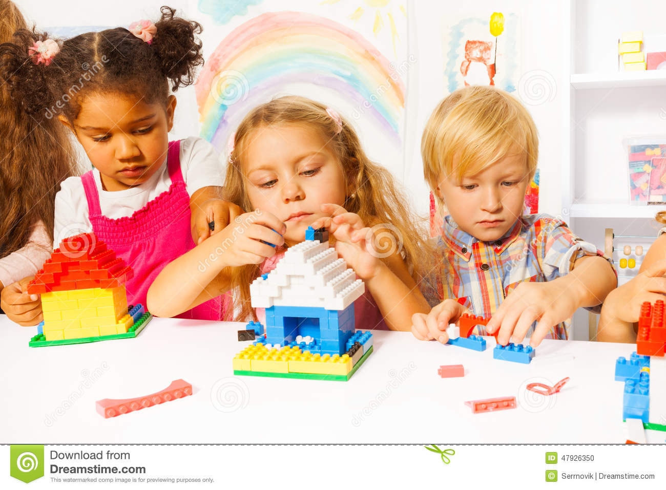 Kinder Garden: Group Of Kids Playing With Plastic Blocks Stock Photo