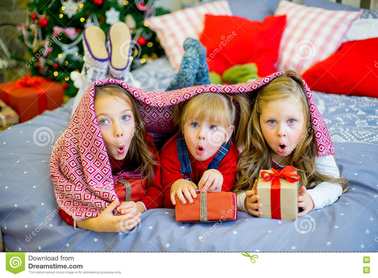 group of kids in red hat lying on the bed next to the christmas tree holding gifts and smiling