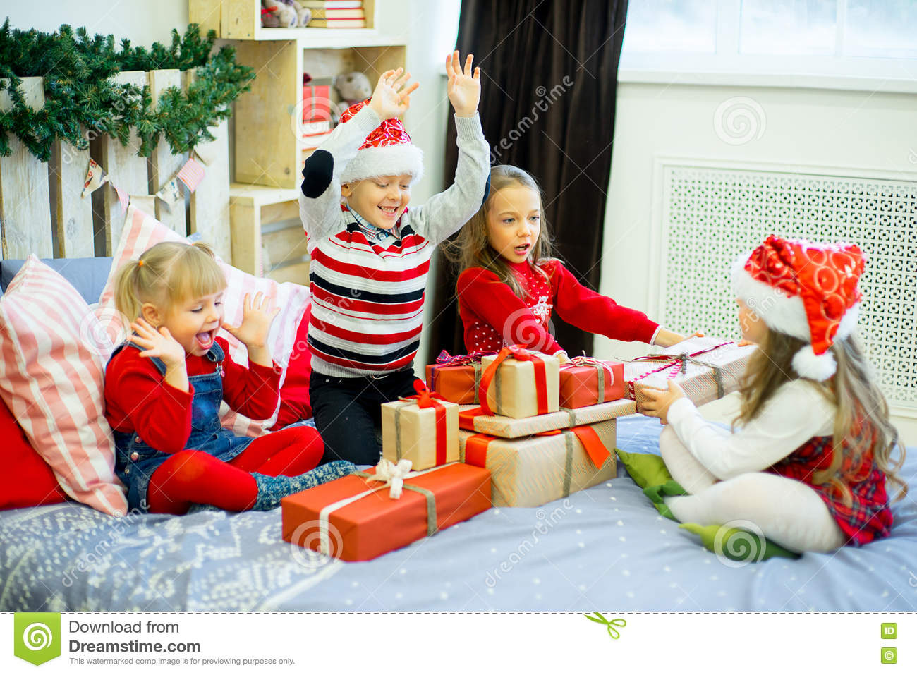 group of kids in red hat sitting on the bed next to the christmas tree holding gifts and smiling