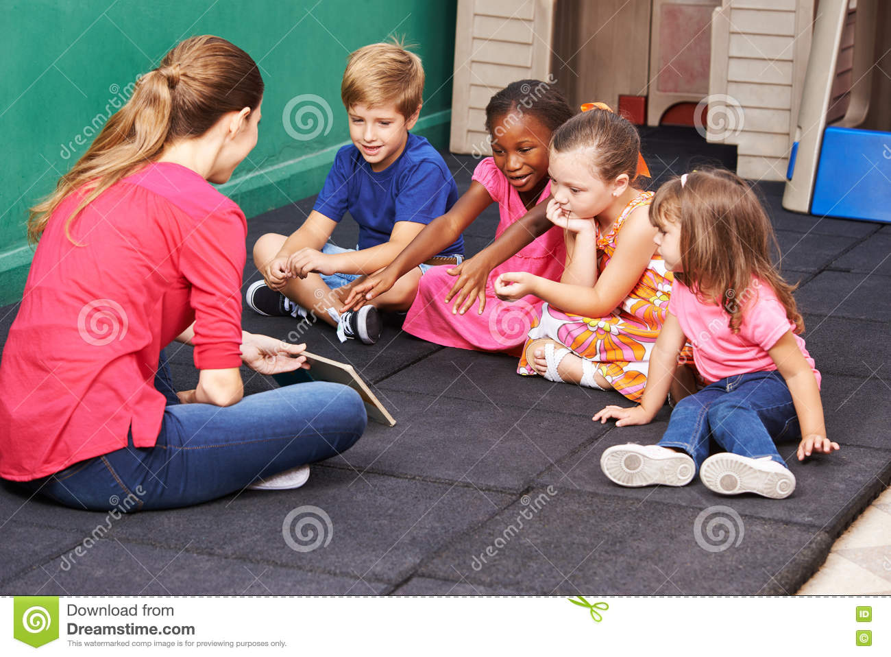 Kinder Garden: Group Of Kids Talking About Book In Preschool Stock Photo