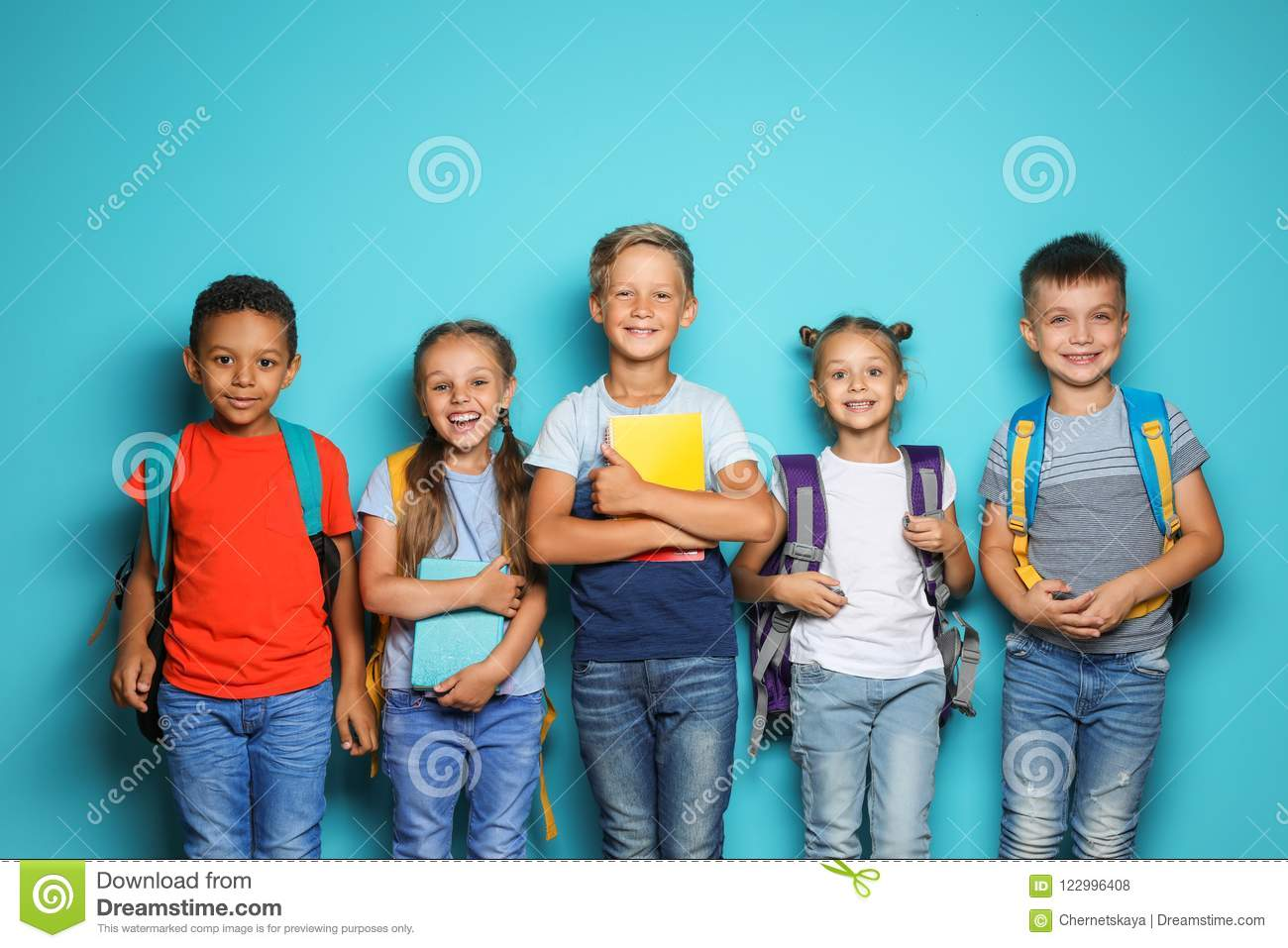 ae02ba104b Group of little children with backpacks and school supplies on color  background