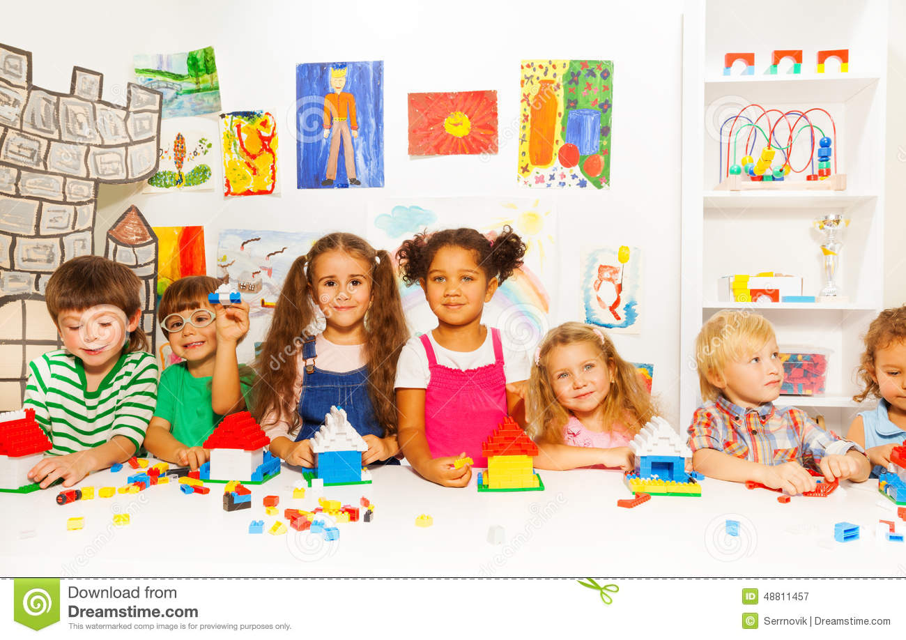 Kinder Garden: Group Of Little Kids Friends Play With Blocks Stock Photo
