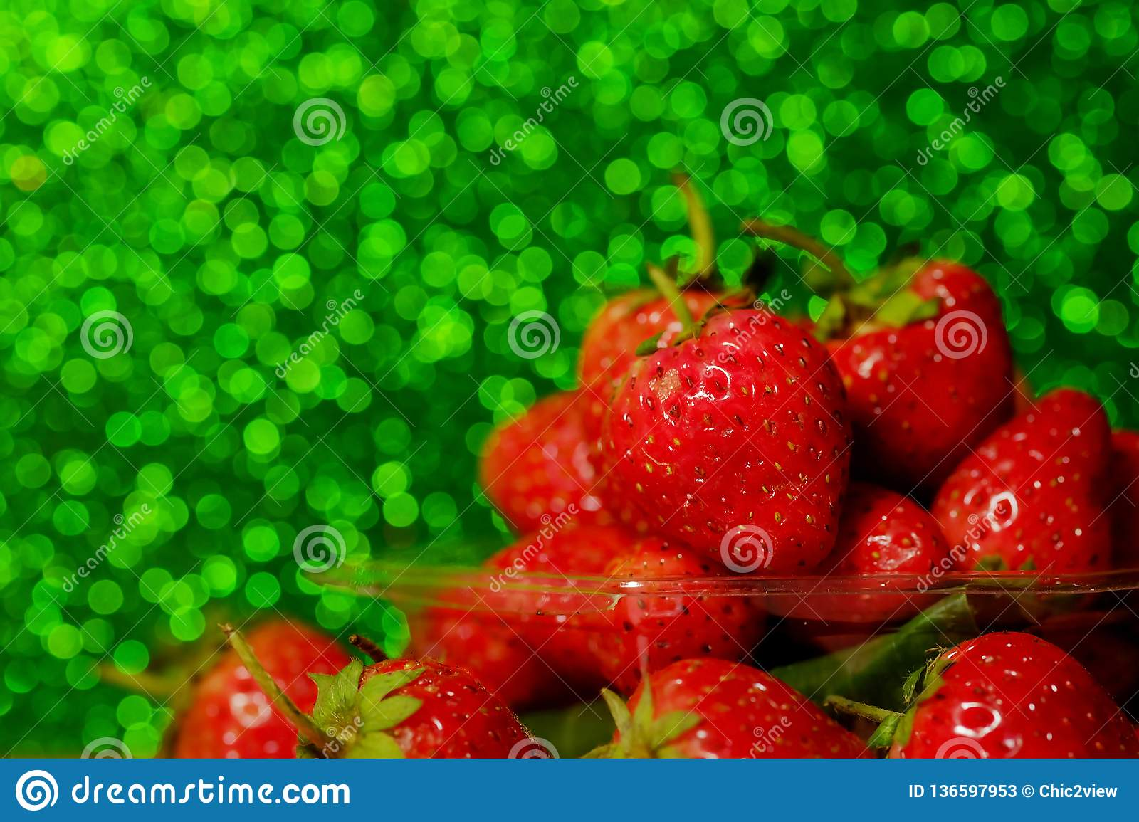 group of little strawberry soft focus with romantic green glitter bokeh background