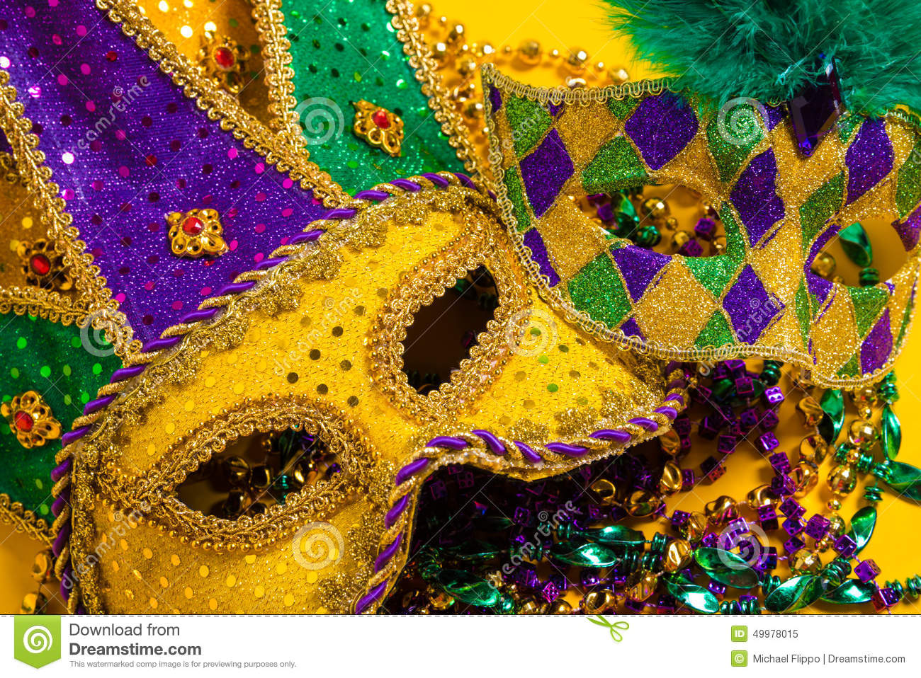 Group of Mardi Gras Masks on yellow Background wtih beads