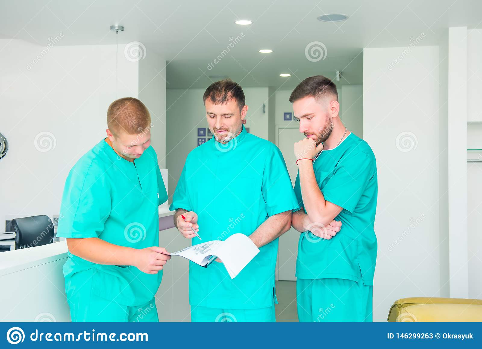 Group of medical staff discussing patient results in clinic. Healthcare professionals having discussion in hospital. Experienced
