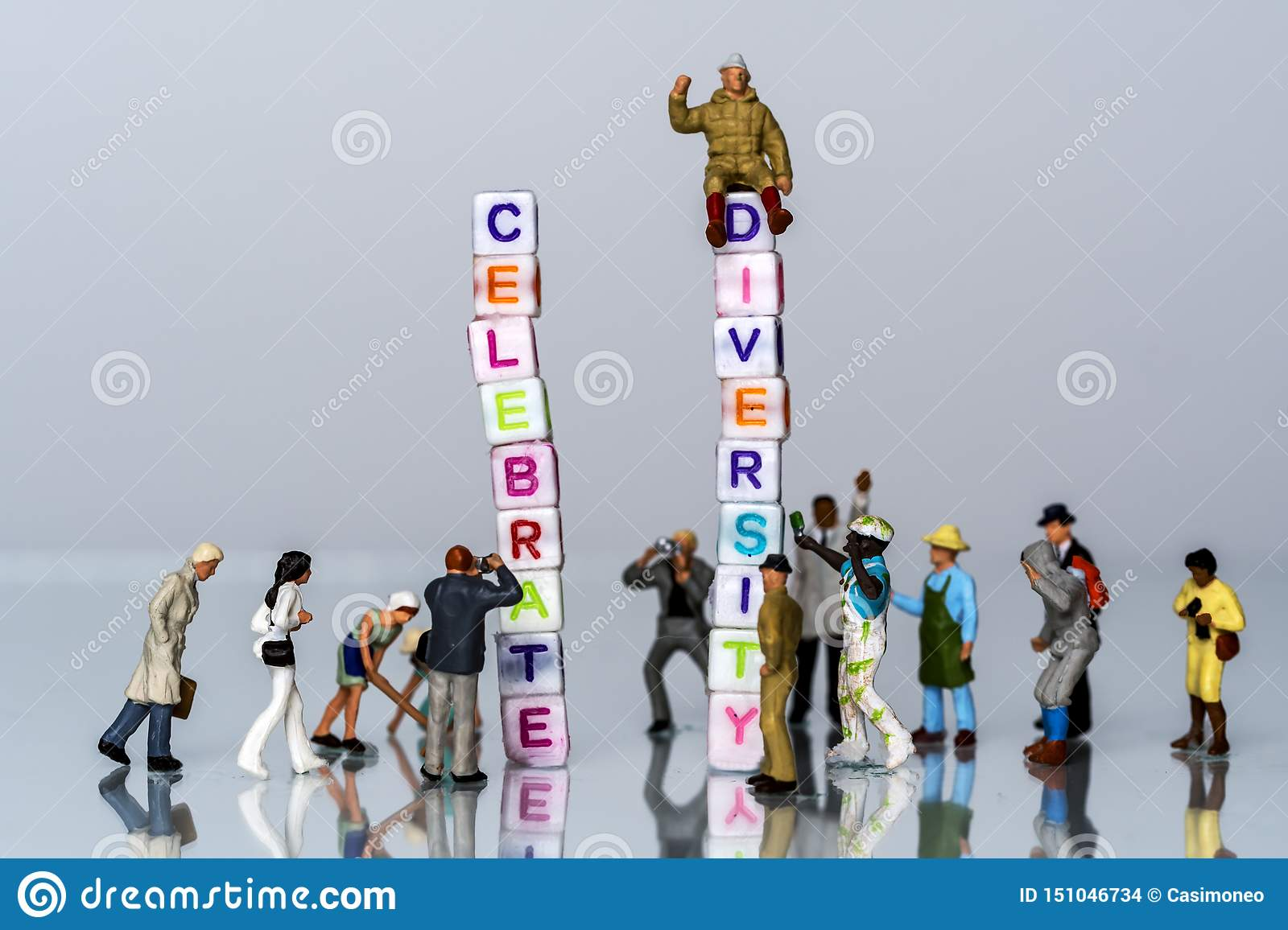 Group of Miniature diverse figurines people walking around a Group Of Letters forming Words Spelling