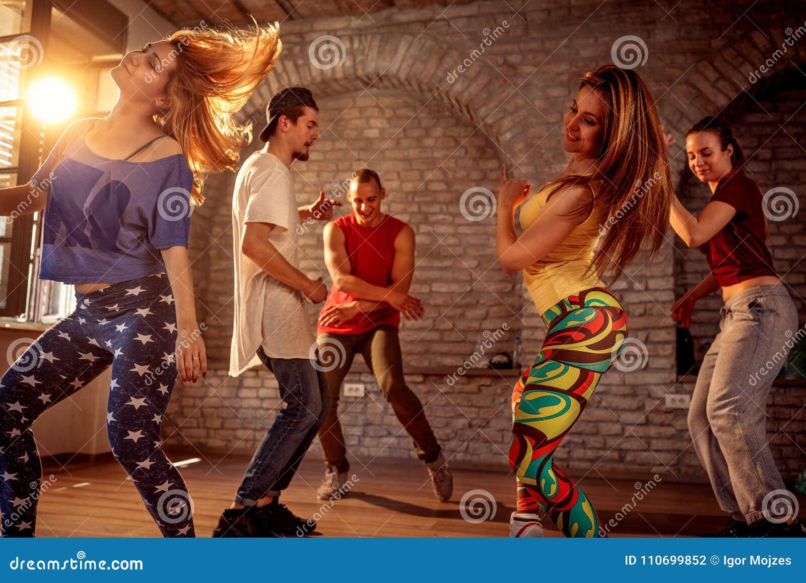 Group of modern street artist break dancers dancing in the studio. Sport, dancing and urban concept