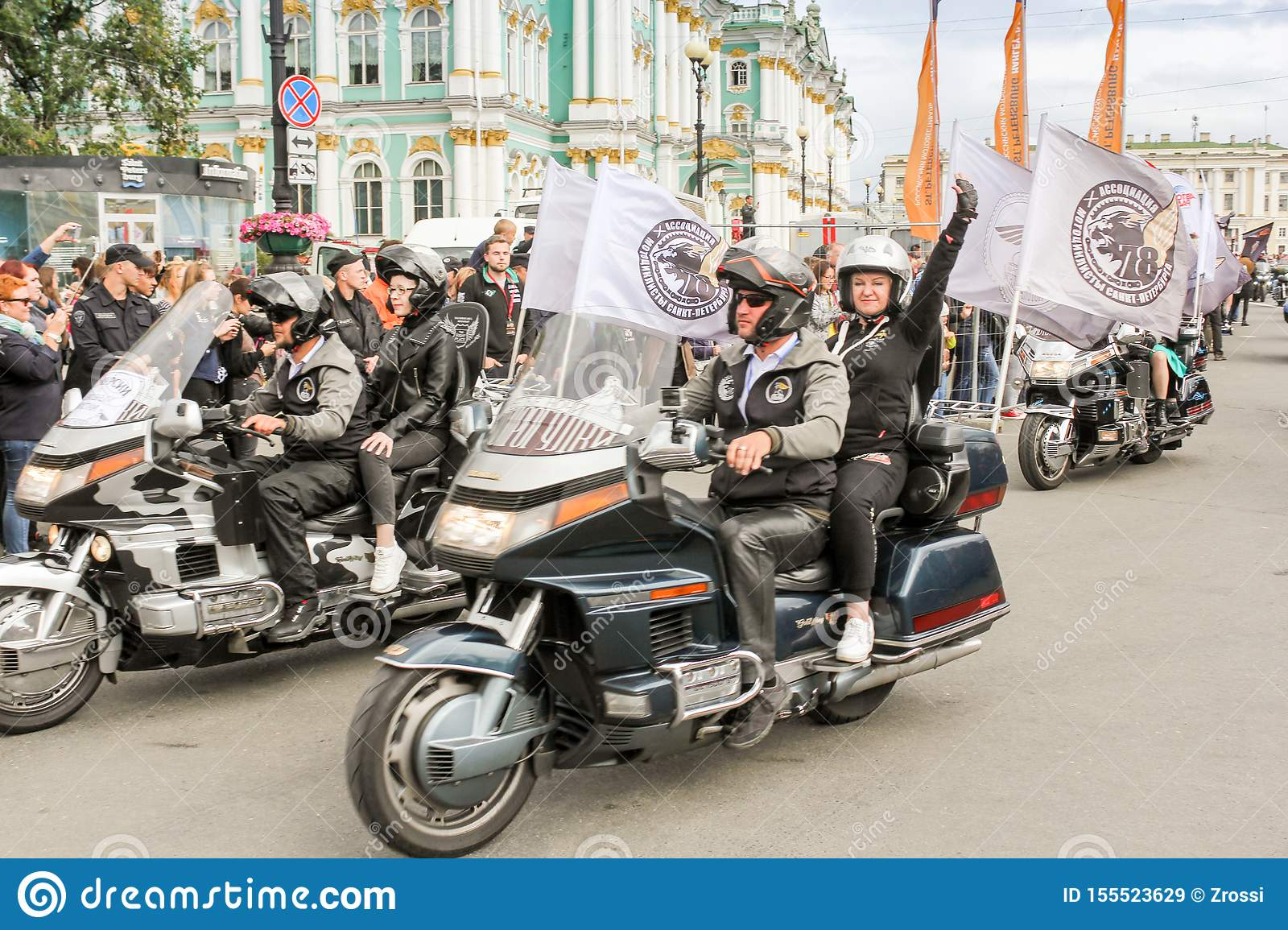 A group of motorcyclists with flags drives by
