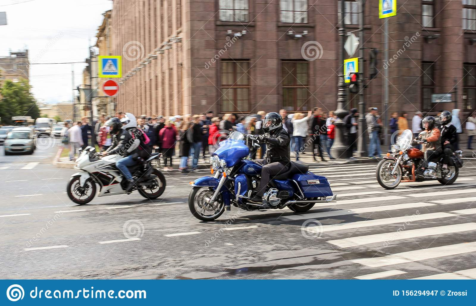 A group of motorcyclists pass by spectators