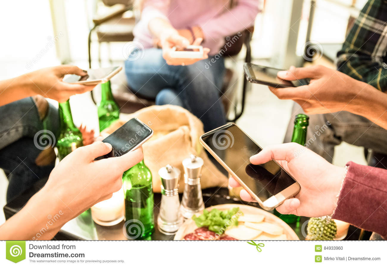 Group of multicultural friends having fun on mobile cell phones