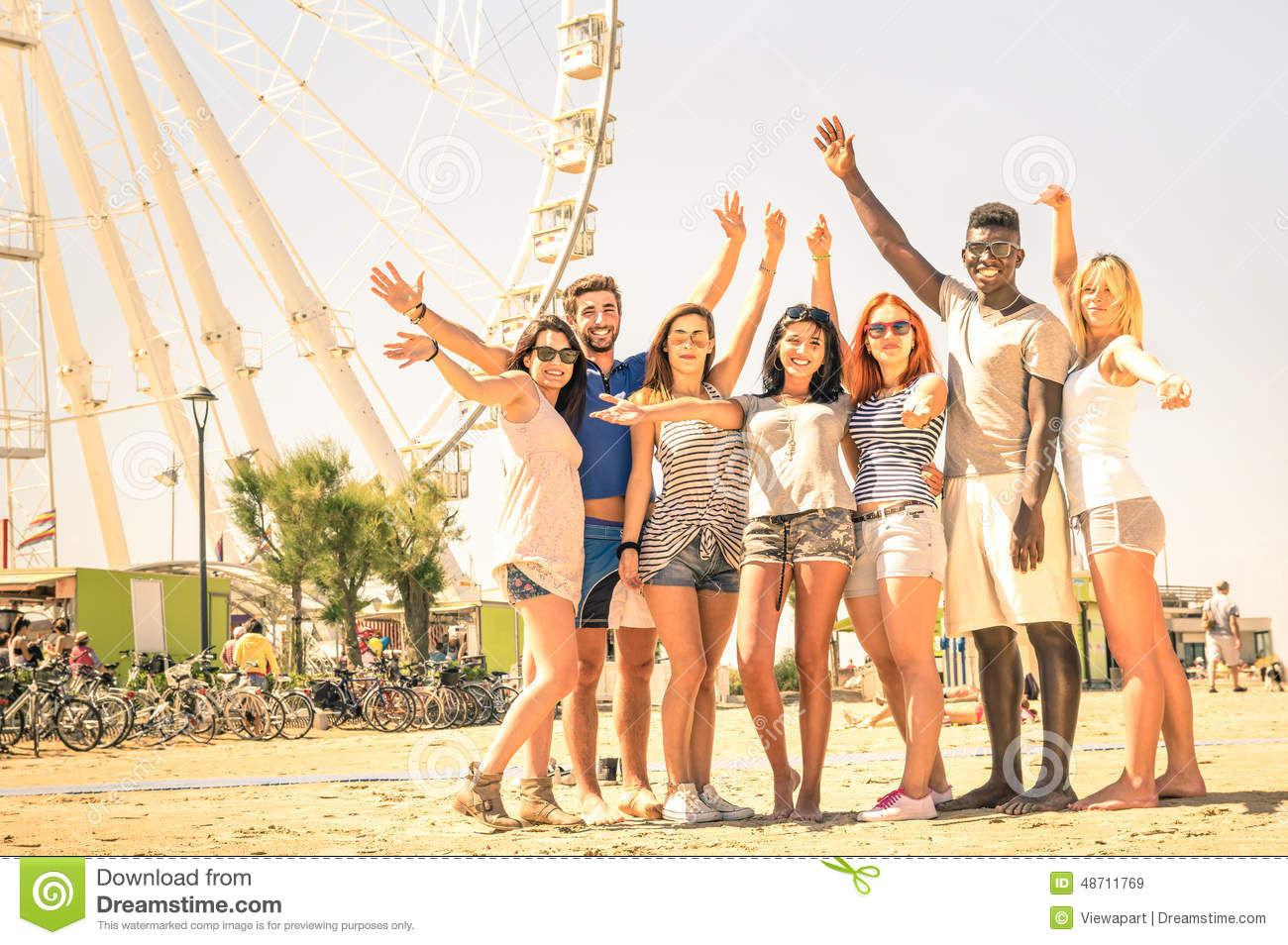 Group of multiracial happy friends cheering at ferris wheel