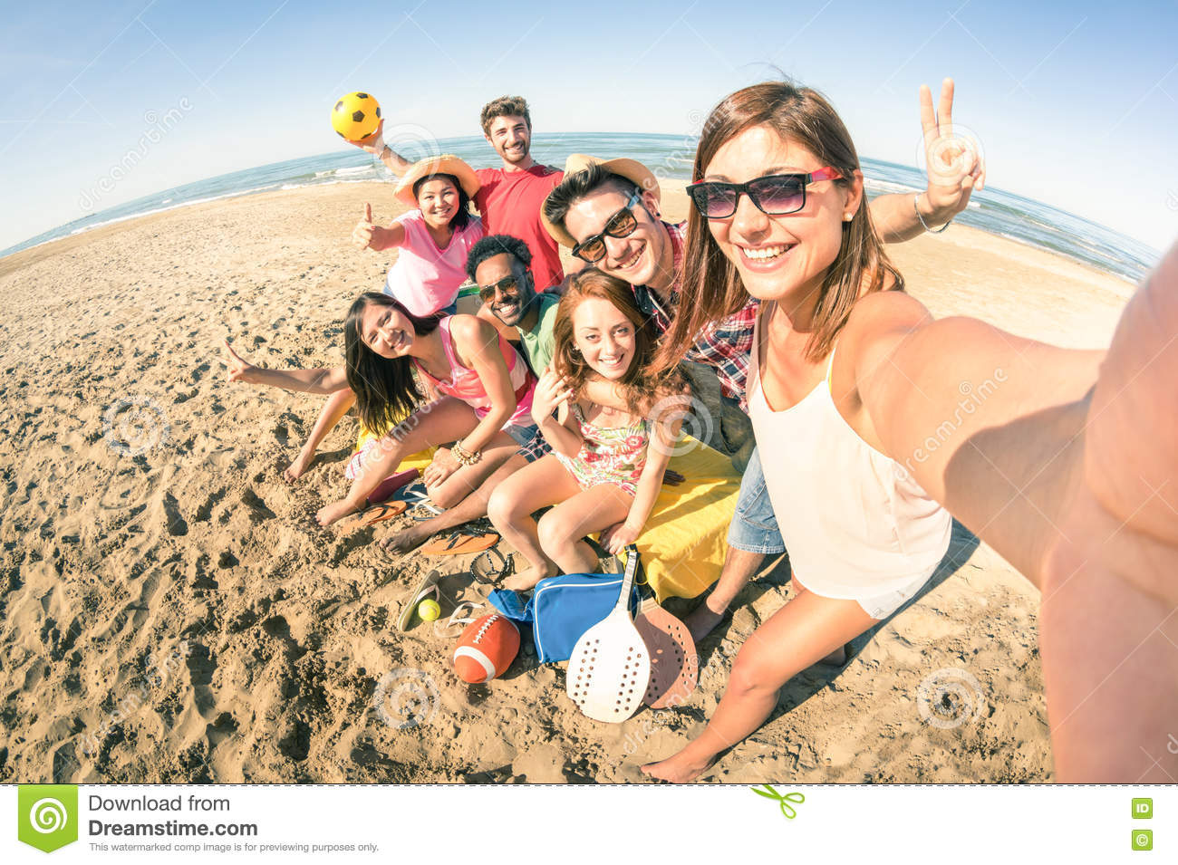 Group of multiracial happy friends taking fun selfie at beach