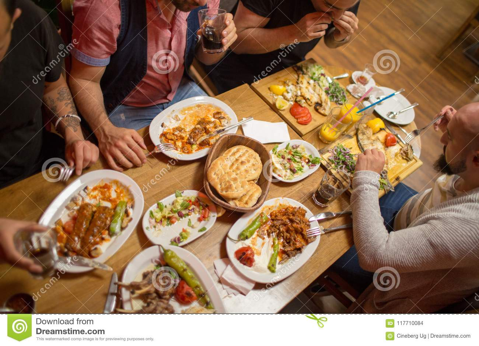 Arab Men In Restaurant Enjoying Middle Eastern Food Stock