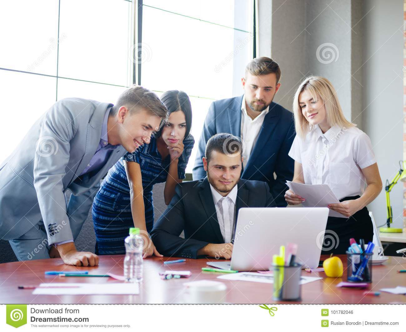 A Group Of Office Workers Examining Ideas On A Laptop Stock Photo