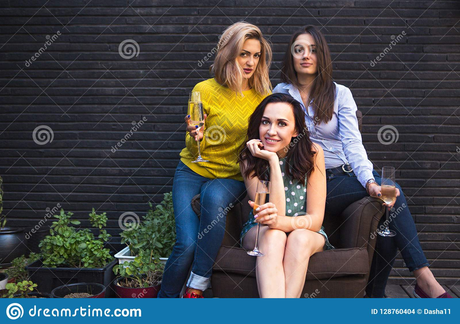 Group of partying girls with flutes with sparkling wine having f