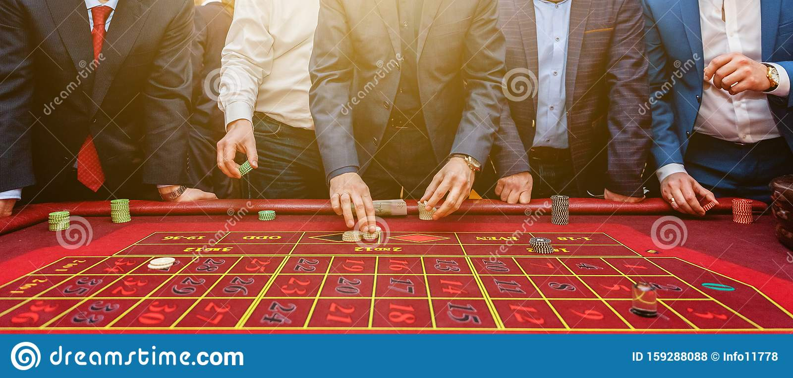 Group Of People Behind Roulette Gambling Table In Luxury Casino