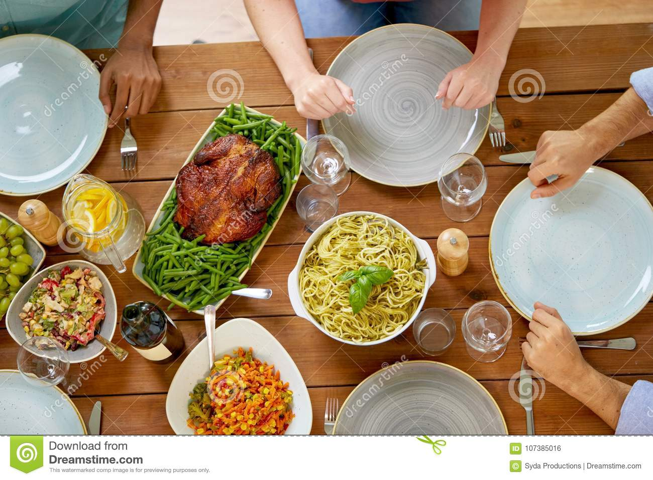 Group of people with chicken and pasta on table