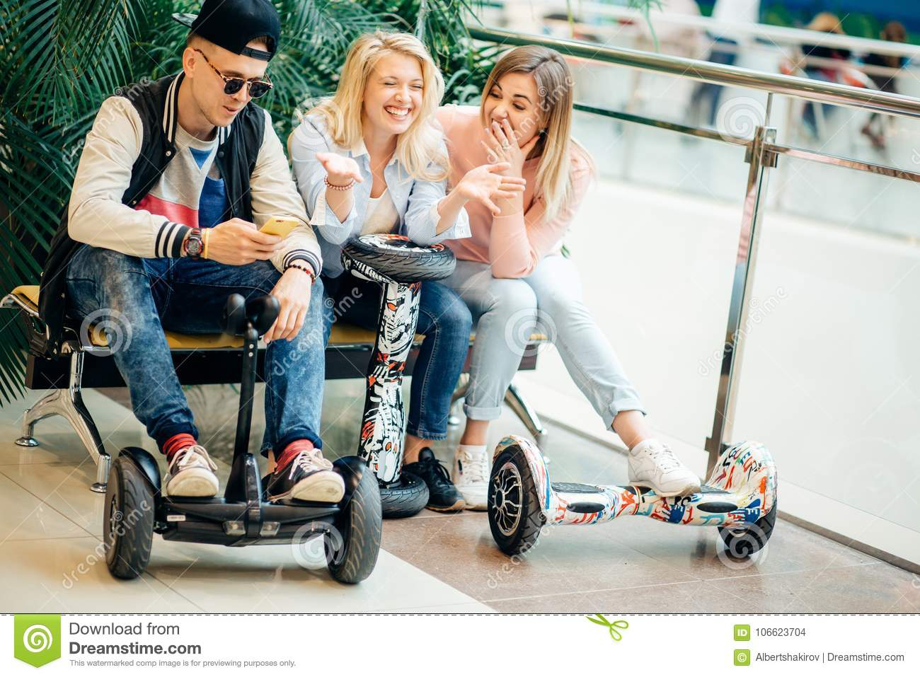 Group Of People On Electric Scooter Hoverboard Sitting At Bench And Using Phone Stock Photo Image Of Lifestyle Group 106623704