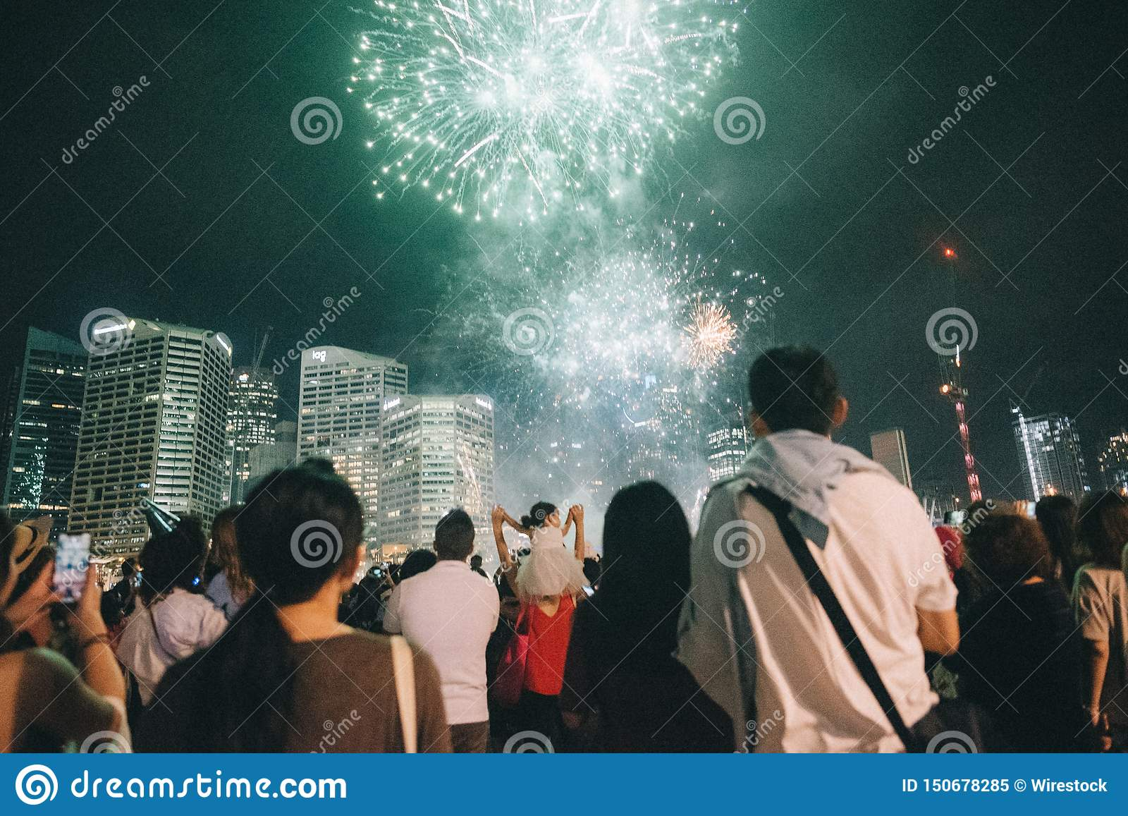 Group of people enjoying beautiful green fireworks at a festival in a park