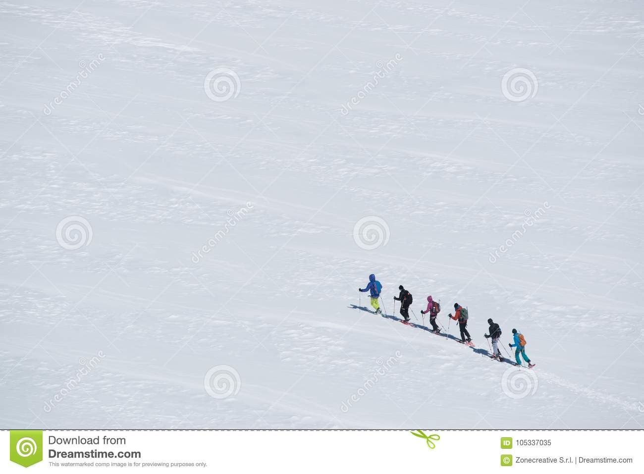 Group of people exploring glacier or snowy land walking with snowshoes. Europe Alps Mont Blanc massif mount. Winter