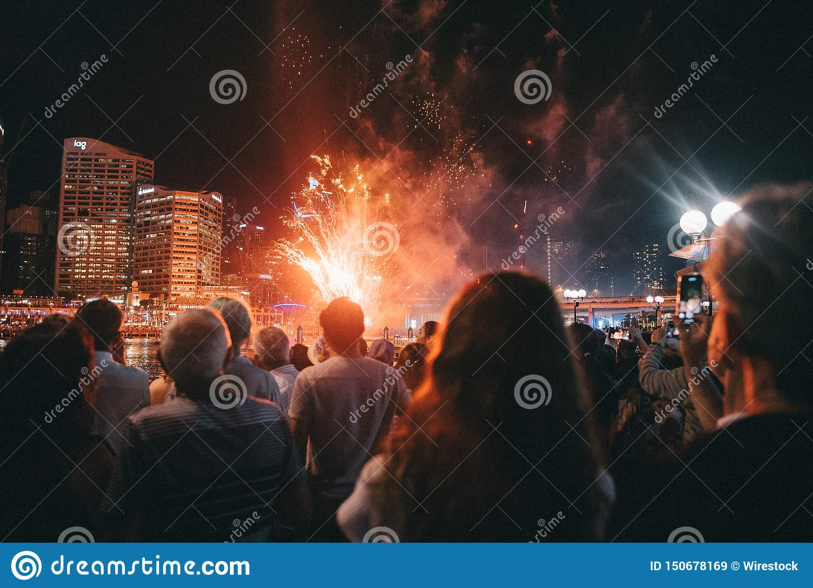 Group of people gathered around at a festival enjoying bright fireworks