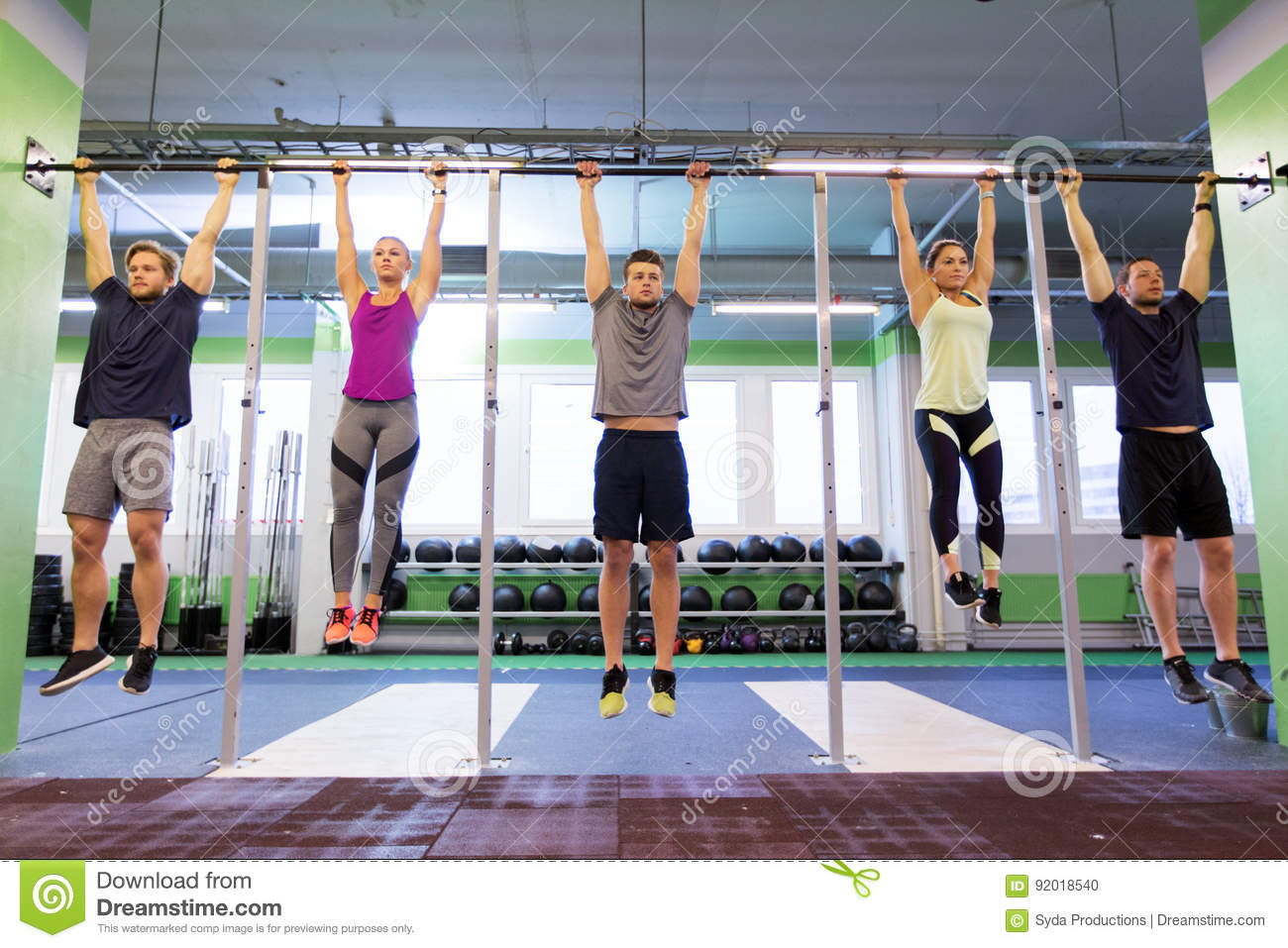 Group Of People Hanging At Horizontal Bar In Gym Stock