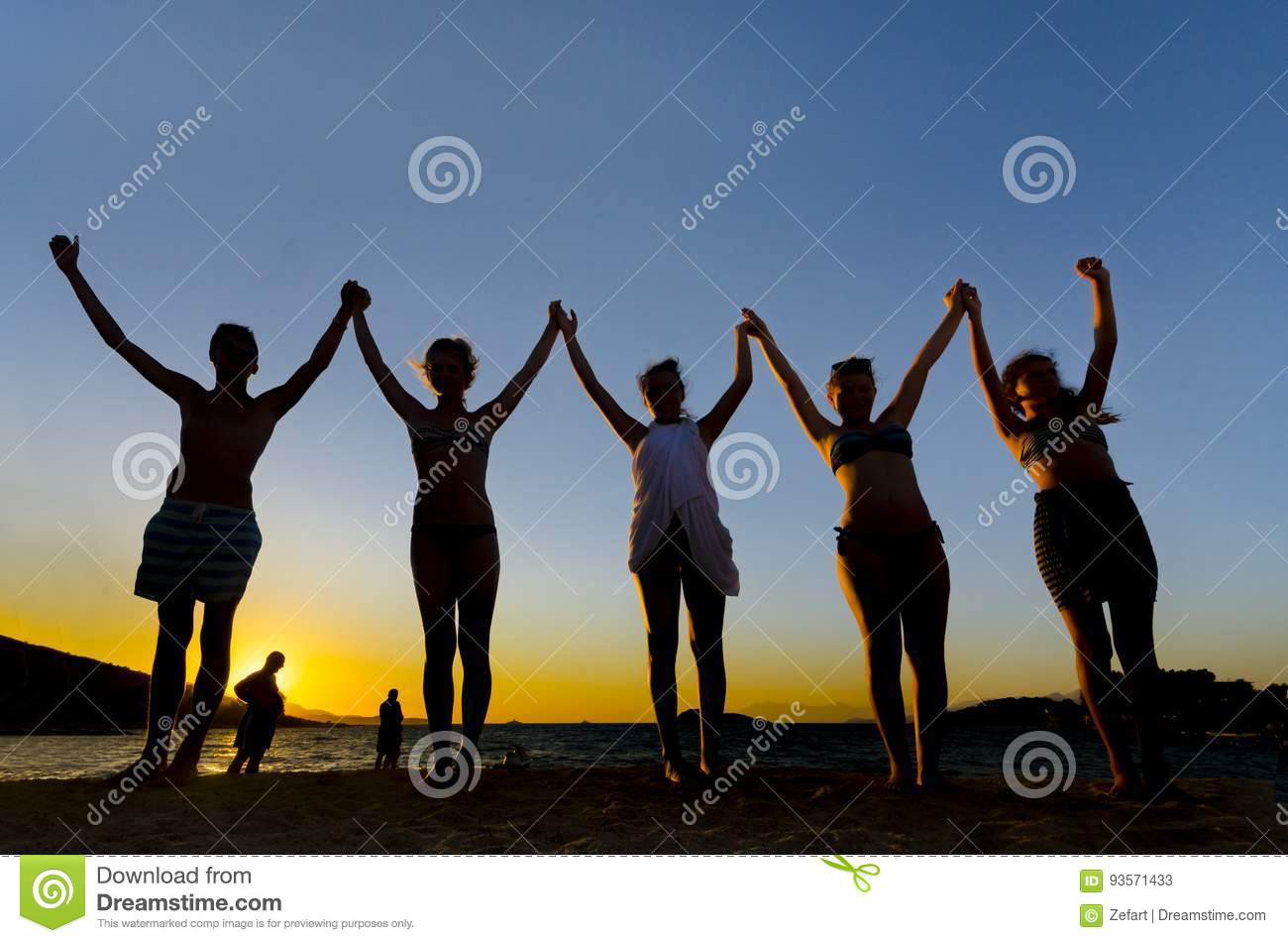 Group of People with Raised Arms backlit by sun