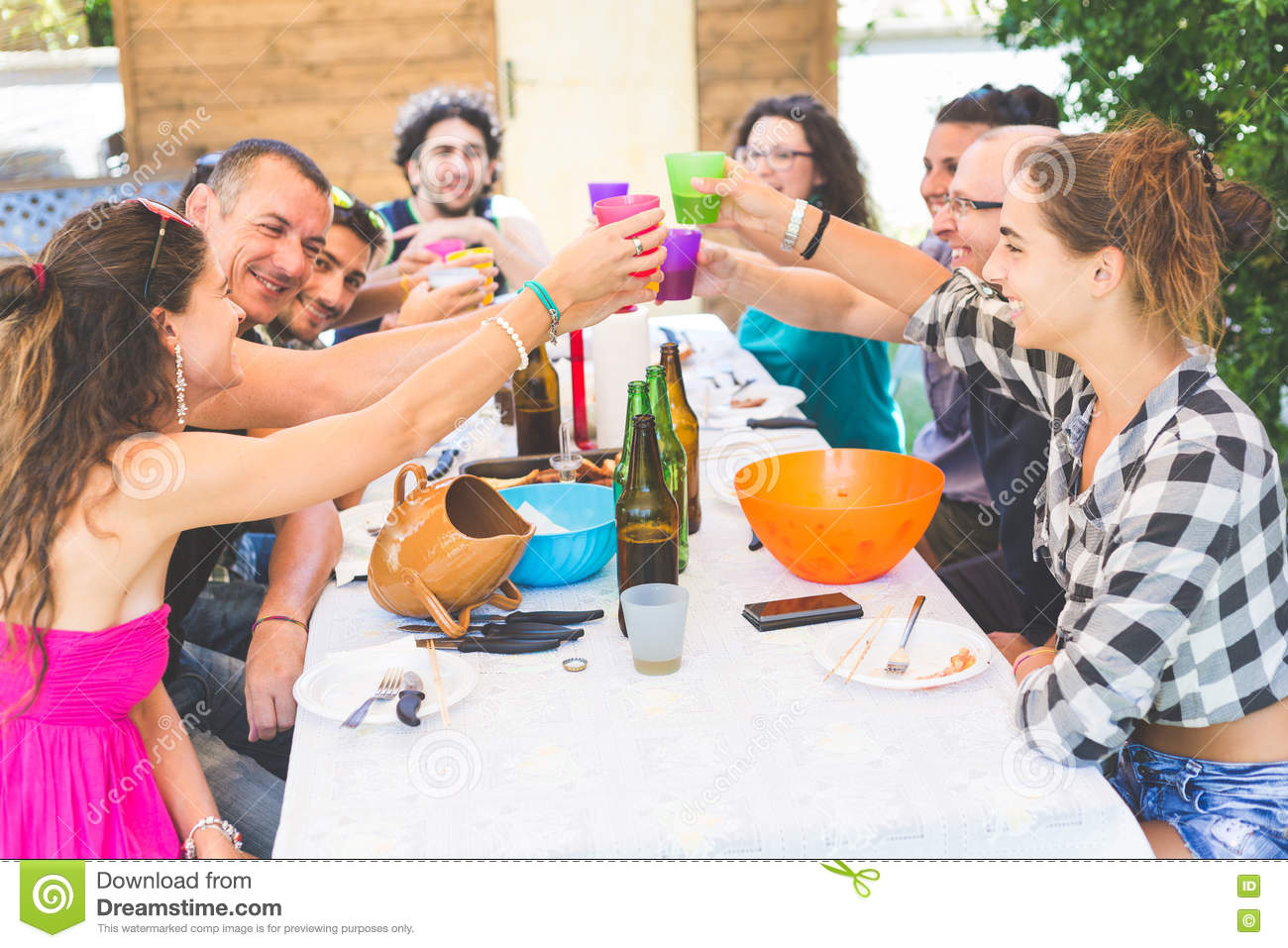 Group of people sitting having lunch together and toasting for Group lunch