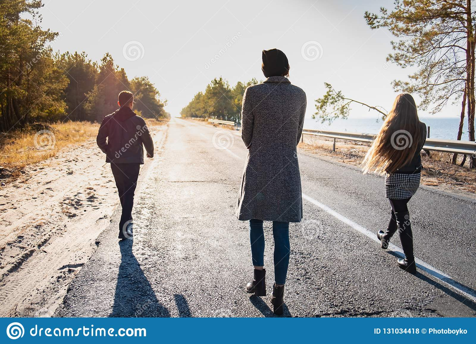 Group of people walk along the road at the seaside. Three young