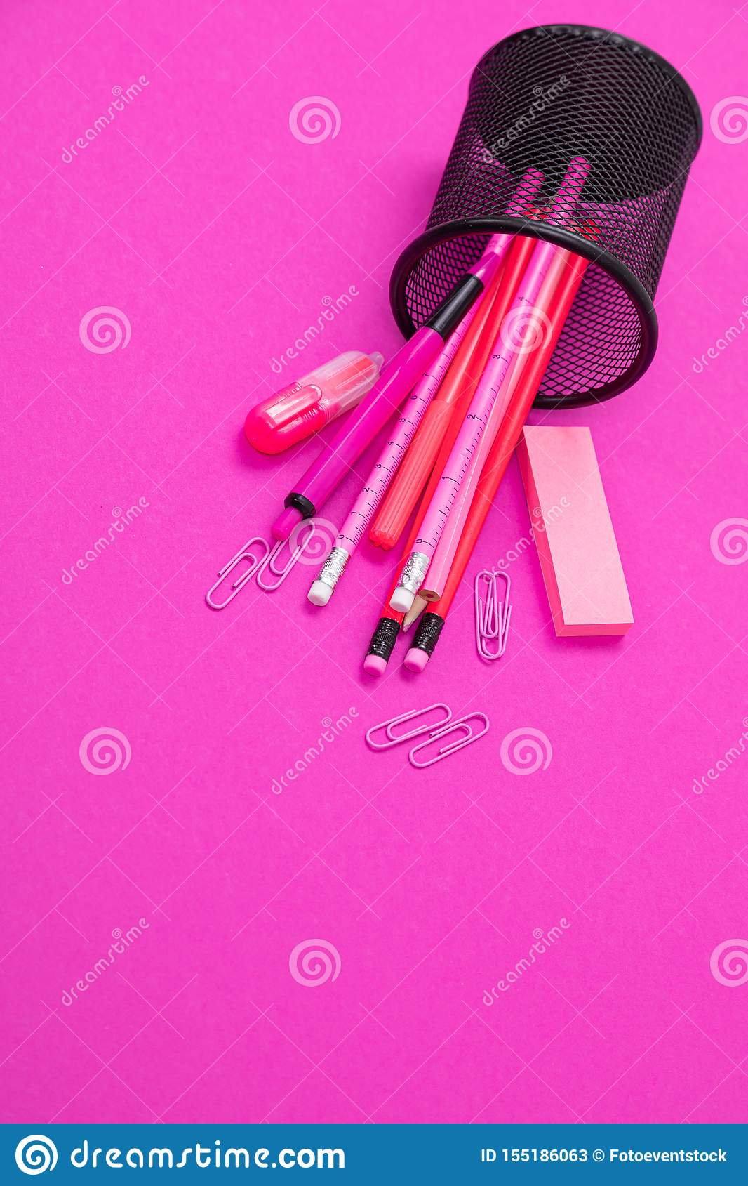 Group of pink color stationery products are scattered from pencil bin from top to bottom on pink background isolated