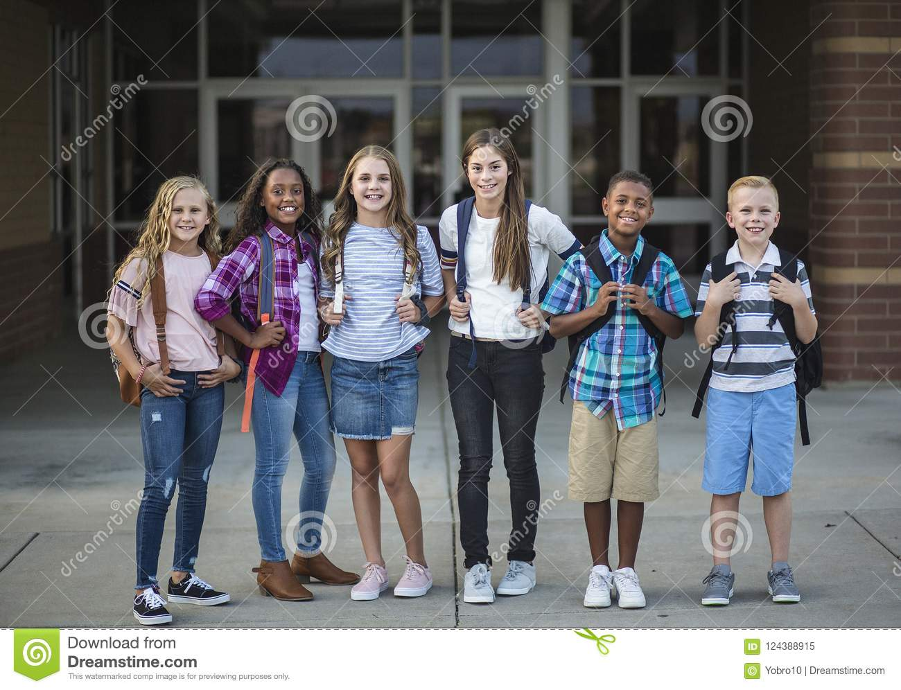 Group portrait of pre-adolescent school kids smiling in front of the school building