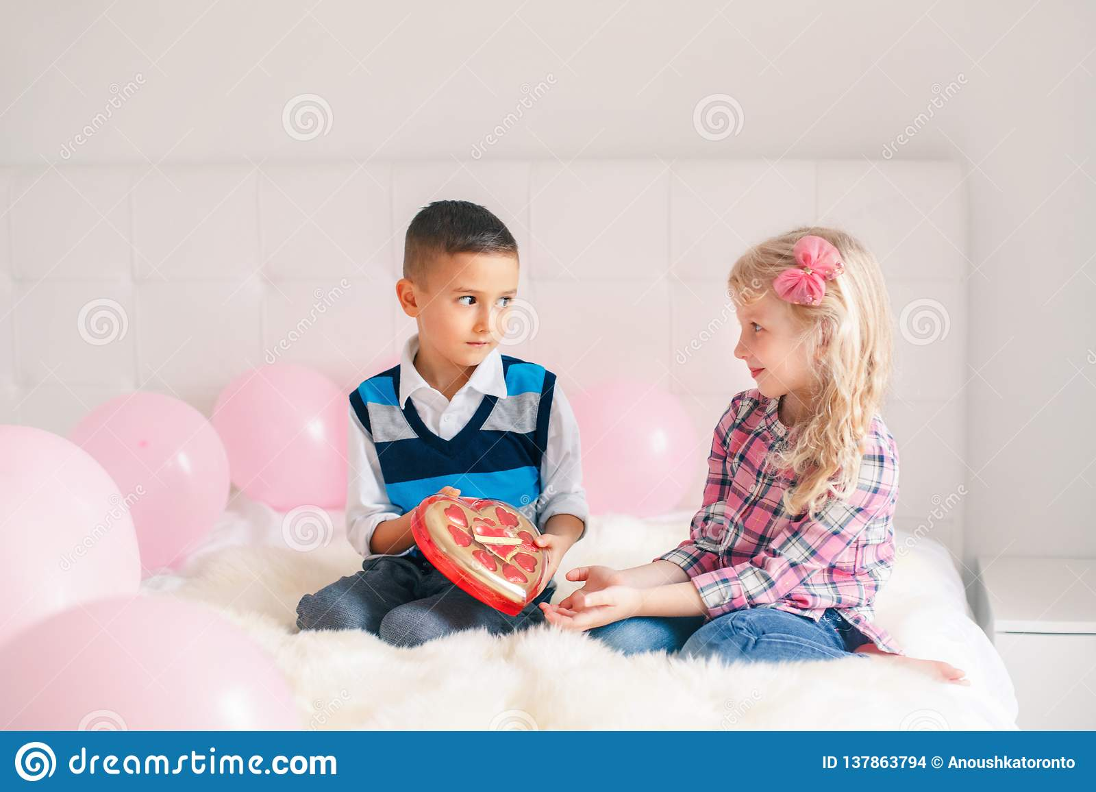 Boy giving girl chocolate gift present to celebrate Valentine Day